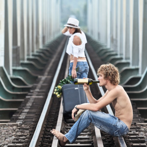 Young woman leaving men on a train tracks